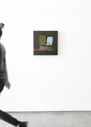 A person walking by a mixed media piece in black, brown, green, and blue by artist Pascal Pierme