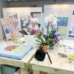 this is the studio of taelor fisher with paintings on a moveable wall and flowers and paints on a table.