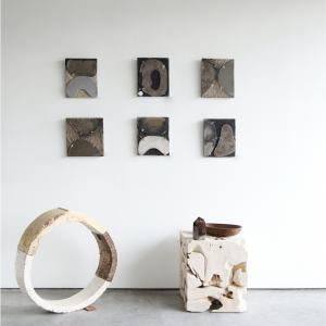 small works in concrete by marlies hoevers.  a round sculpture by brandon reese sits on the floor next to a teak square table.