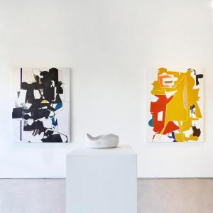 two large aaron wexler abstract collages behind a yasha butler ceramic vesssel