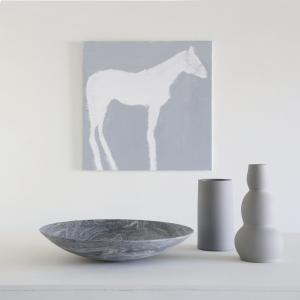 a grey and white painting of a horse by artist julie sneed with grey stone bowl and grey vases on a table