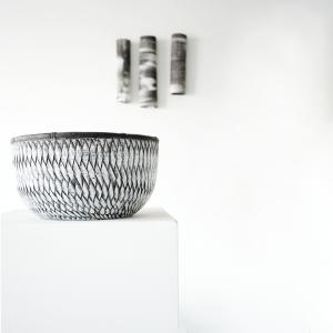 3 cylinders made by ceramic artist jodi walsh are on the wall behind a wood bowl that is ebony and white