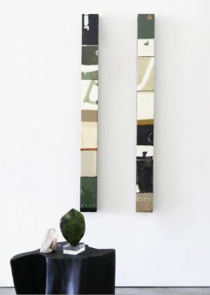 A gallery wall of narrow tall  paintings by artist Silvia Poloto in green, black and white with a teak table, and green obsidian piece sitting in front of it.